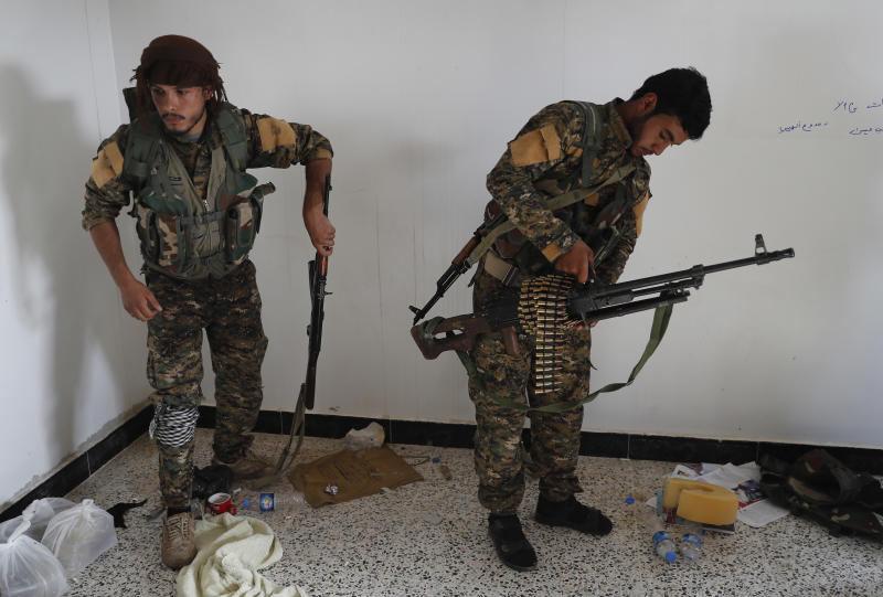 FILE - In this July 22, 2017 file photo, an Arab fighter, left, and Kurdish fighter, right, who fight together with the U.S.-backed Syrian Democratic Forces (SDF), hold their weapons as they prepare to move to the front line to battle against the Islamic State militants, in Raqqa, northeast Syria. A year after it was routed from Iraq following a three-year devastating war that left Iraqi cities in ruin, the Islamic State group is fighting to hang on to its last enclave in Syria, engaging in deadly battles with U.S.-backed forces in the country's east near the Iraqi border. (AP Photo/Hussein Malla, File)