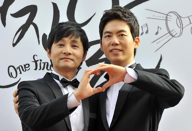 Film director Kim Jho Gwang-Soo (L) and his partner Kim Seung-Hwan pose during a press conference before their wedding in central Seoul on September 7, 2013 (AFP Photo/Jung Yeon-Je)