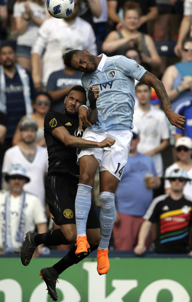 Sporting Kansas City forward Khiry Shelton (14) heads the ball over Columbus Crew midfielder Artur, left, during the first half of an MLS soccer match in Kansas City, Kan., Sunday, May 27, 2018. (AP Photo/Orlin Wagner)