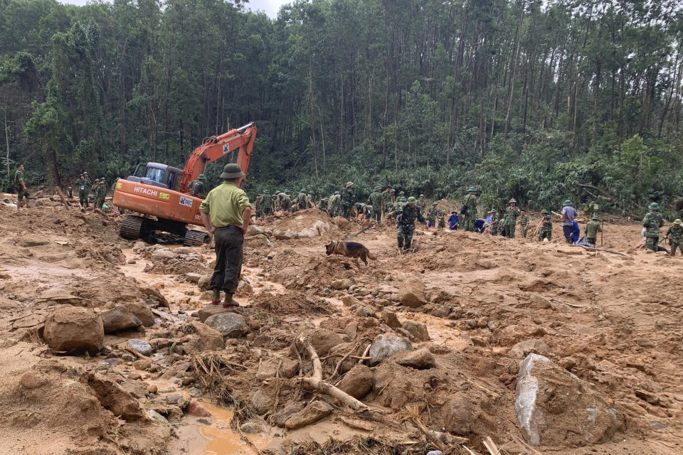 Rescue workers recover bodies of army officers buried in a landslide in Thua Thien-Hue province, Vietnam, Thursday, Oct. 15, 2020. Rescuers recovered the bodies of 11 army personnel and two other people who were buried in the landslide while trying to reach victims of another landslide, state media reported Friday, Oct. 16, 2020. (Tran Le Lam/VNA via AP)