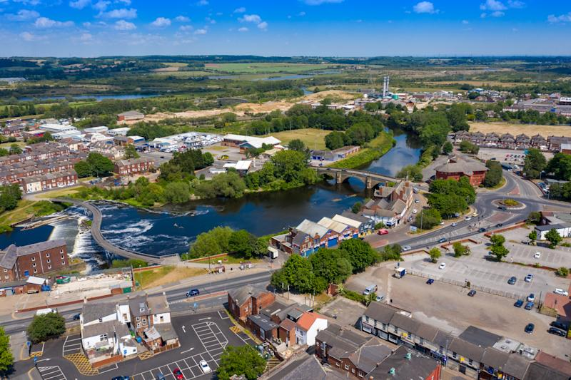 Aerial photo of the village centre of Castleford in Wakefield, West Yorkshire, England showing the main street along side the River Aire on a bright sunny summers day