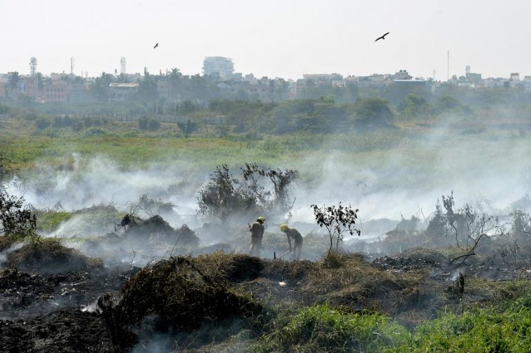 Firefighters work at the polluted Bellandur Lake that has become so toxic it spontaneously catches fire