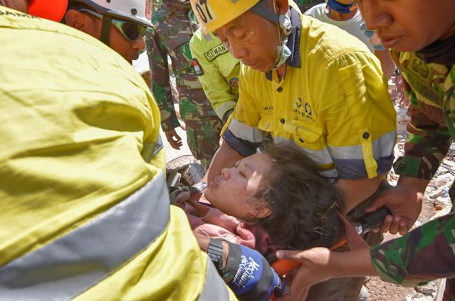 <p>Rescue workers and soldiers carry a woman, who survived after being trapped in rubble since Sunday's earthquake, in Tanjung, North Lombok, Indonesia, Aug. 7, 2018. (Photo: Antara Foto/Zabur Karuru via Reuters) </p>