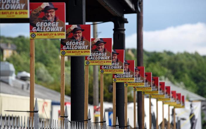 George Galloway Batley and Spen by-election posters arranged in a long row outside campaign headquarters in Bradford Road, Batley. - Asadour Guzelian/Guzelian