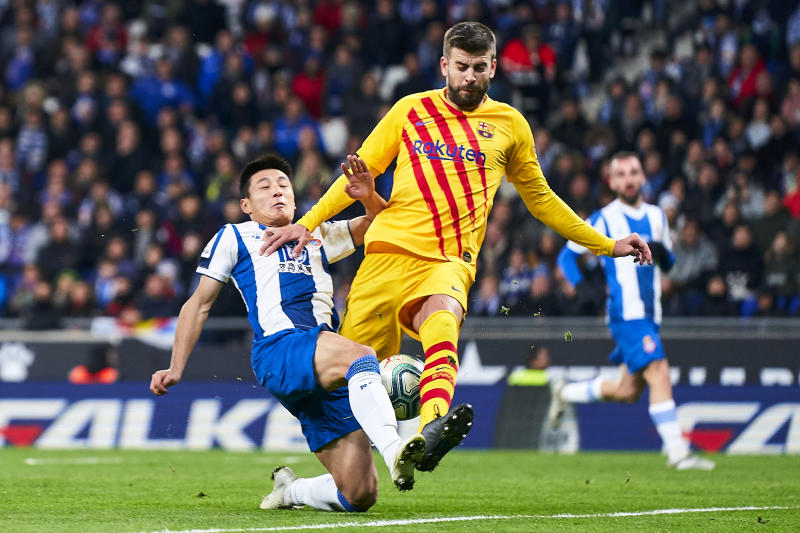 BARCELONA, SPAIN - JANUARY 04: Wu Lei of RCD Espanyol competes for the ball with Gerard Pique of FC Barcelona during the Liga match between RCD Espanyol and FC Barcelona at RCDE Stadium on January 04, 2020 in Barcelona, Spain. (Photo by Quality Sport Images/Getty Images)