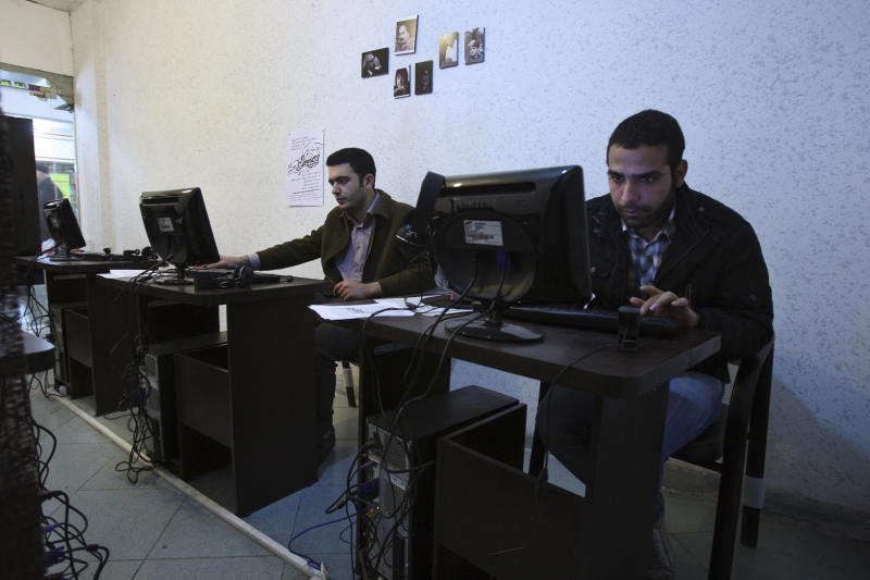 """In this picture taken on Tuesday, Jan. 18, 2011, Iranian journalism students use computers in an internet cafe in central Tehran, Iran. Iran calls it the """"soft war"""" with the West: Battles to control, defend and monitor the web and telecommunications. The latest move came from the Revolutionary Guard, launching what they claim is a hack-proof phone network for high-level commanders. Tehran's efforts to build a cyber-fortress have become a priority among leaders fearful of Internet espionage and virus attacks from abroad and seeking to choke off opposition voices at home. (AP Photo/Vahid Salemi)"""