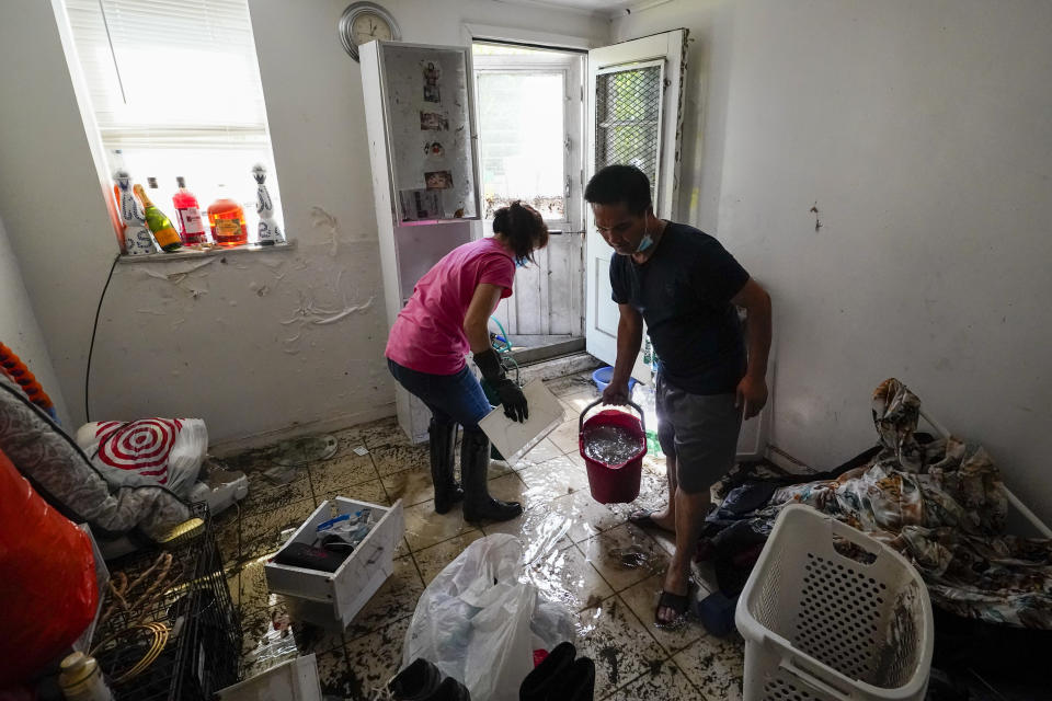 Residents of Peck Ave in the Flushing neighborhood of the Queens borough of New York use buckets to remove water from their basement apartment, Thursday, Sept. 2, 2021, in New York. The remnants of Hurricane Ida dumped historic rain over New York City, with several deaths linked to flooding in the region as basement apartments suddenly filled with water and freeways and boulevards turned into rivers, submerging cars.(AP Photo/Mary Altaffer)