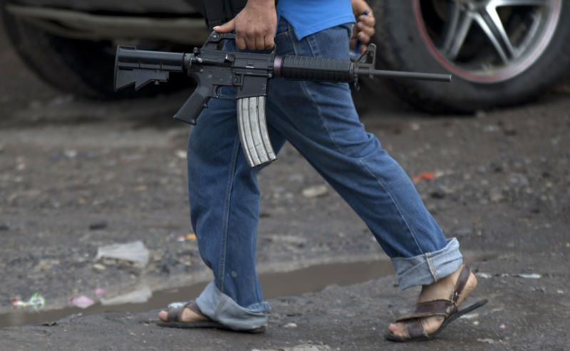 A man from the Self-Defense Council of Michoacan, (CAM), carries his weapon at a checkpoint set up by the self-defense group at the entrance to the town of Antunez, Mexico, Thursday, Jan. 16, 2014. Vigilantes in Michoacan state insist they won't lay down their guns until top leaders of a powerful drug cartel are arrested, defying government orders as federal forces try to regain control in a lawless region plagued by armed groups. (AP Photo/Eduardo Verdugo)