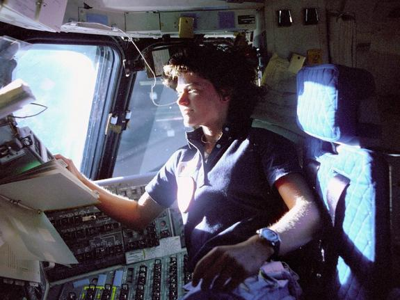 The first U.S. woman in space, Sally Ride, monitors control panels from the pilot's chair on the Flight Deck of the STS-7 mission.