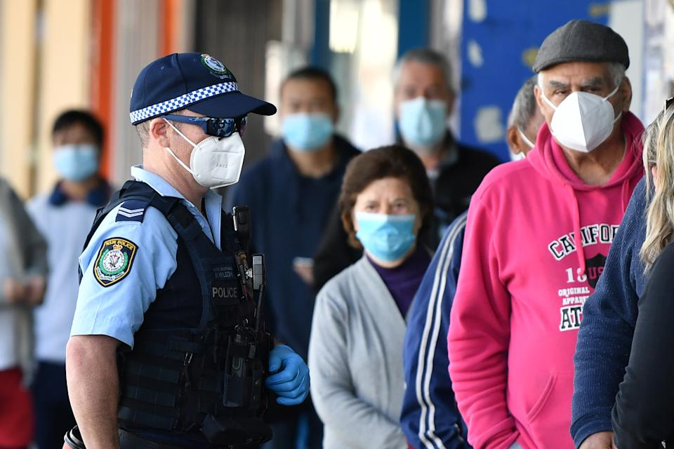 Members of the public wearing face masks wait outside a bank at Campsie in Sydney. Source: AAP