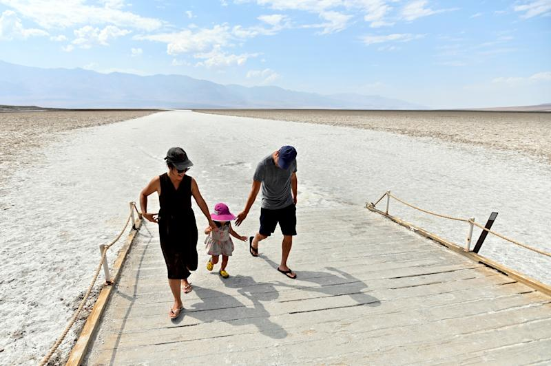 Ramona Fong and her husband Kenzo Fong walk along the boardwalk with their daughter, Rumi, 2, at Badwater Basin, in Death Valley National Park, California.