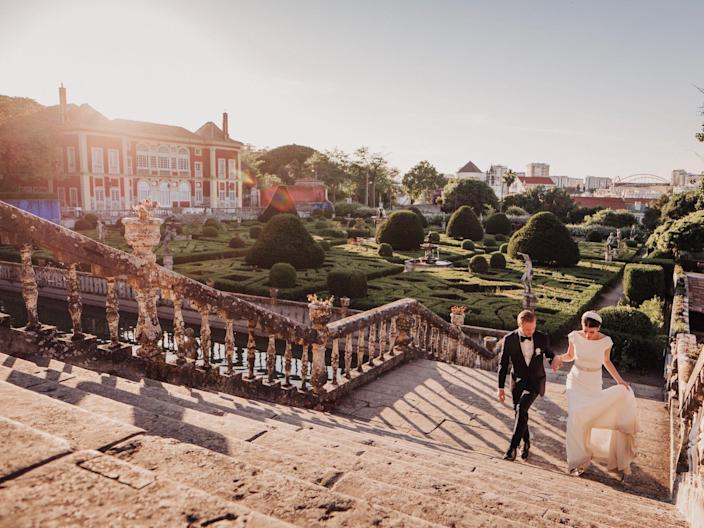 A groom helps a bride walk up a set of stairs next to an extravagant garden and home.