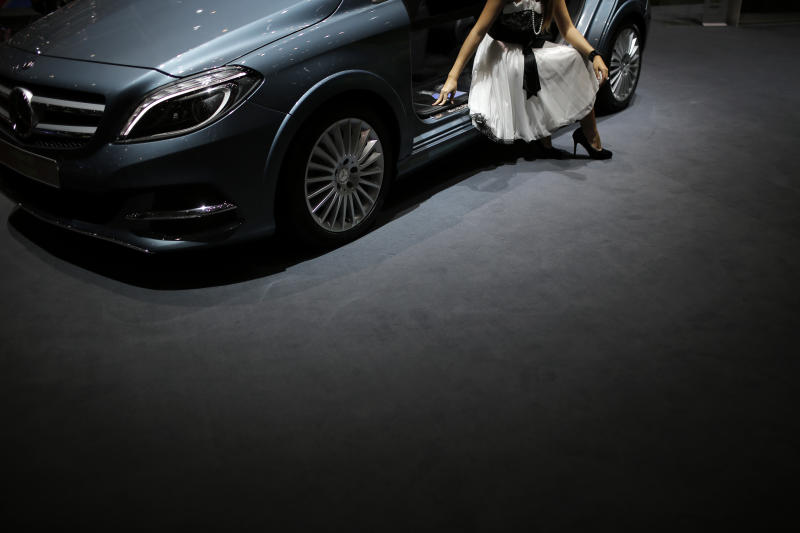 A hostess poses in a car during the first media day of the 83rd Geneva International Motor Show, Switzerland, Tuesday, March 5, 2013. The Motor Show will open its gates to the public from March 7 to 17.  (AP Photo/Laurent Cipriani)