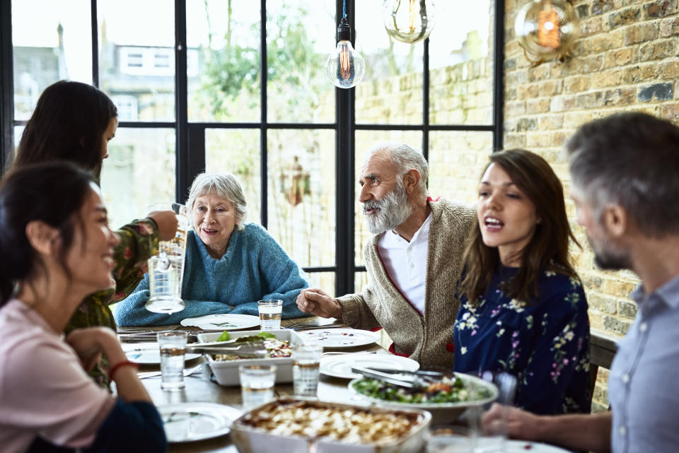 Mixed age ranges enjoying meal together in family home, pre teen girl pouring water for dinner guests, social vibrant lively family gathering