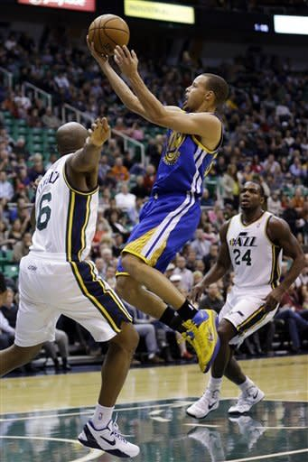 Golden State Warriors guard Stephen Curry, center, lays the ball up as Utah Jazz point guard Jamaal Tinsley (6) defends and forward Paul Millsap (24) watches in the first quarter of an NBA basketball game, Wednesday, Dec. 26, 2012, in Salt Lake City. (AP Photo/Rick Bowmer)