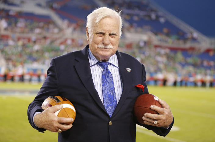 In this Dec. 23, 2014 photo, former Florida Atlantic and Miami head coach, Howard Schnellenberger holds the game balls prior to the start of the Boca Raton Bowl NCAA college football game between Marshall and Northern Illinois at FAU Stadium in Boca Raton, Fla. Schnellenberger, who coached Miami to the 1983 national championship and built programs at Louisville and Florida Atlantic, died Saturday, March 27, 2021, at the age of 87, Florida Atlantic announced. (AP Photo/Joel Auerbach)