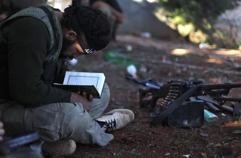 FILE - In this Thursday, Nov. 15, 2012 file photo, a Syrian rebel reads the Quran during clashes with government forces in Aleppo, Syria. President Barack Obama said early on in the 2 1/2-year-old conflict that Assad lost the right to lead because of the brutal oppression of his people, most chillingly displayed in what Washington contends was an Aug. 21 chemical weapons attack on rebel-held areas that killed hundreds of civilians. But it's not clear who would replace Assad if he were to be driven from power, either as a result of U.S. punitive strikes for the suspected poison gas attacks or in eventual political transition talks with the Western-backed opposition. (AP Photo/ Khalil Hamra, File)