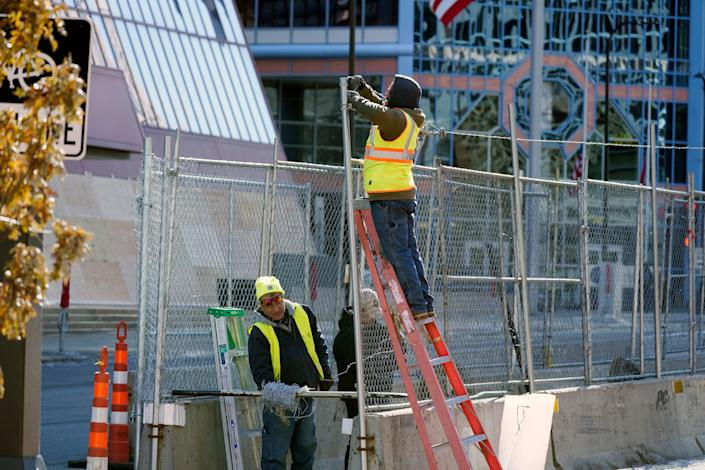 Workers install barbed wire on fencing outside the Hennepin County Government Center, Wednesday, Feb. 23, 2021 in Minneapolis, as part of security preparation for the trial of former Minneapolis police officer Derek Chauvin. The trial is slated begin with jury selection on March 8. Chauvin is charged with murder the death of George Floyd during an arrest last May in Minneapolis. (AP Photo/Jim Mone) (AP)