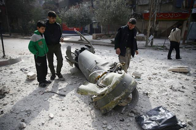 <p>People inspect missile remains in the besieged town of Douma, in eastern Ghouta, in Damascus, Syria, Feb. 23, 2018. (Photo: Bassam Khabieh/Reuters) </p>