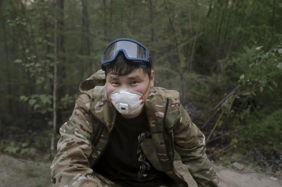 Mikhail Zhirkov, member of volunteers crew speaks during his interview with the Associated Press at Gorny Ulus area west of Yakutsk, Russia, Thursday, July 22, 2021. More than 5,000 regular firefighters are involved, but the scale of the blazes is so large and the area is so enormous that 55% of the fires aren't being fought at all, according to Avialesookhrana, the agency that oversees the effort. That means the volunteers, who take time off work and rely on their own money or nongovernmental funds, are a small but important addition to the overwhelmed forces. (AP Photo/Ivan Nikiforov)
