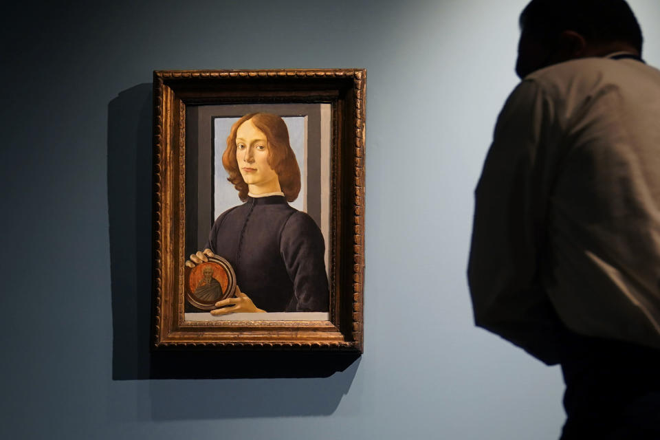 """FILE — In this Sept. 23, 2020, file photo, Sandro Botticelli's 15th-century painting called """"Young Man Holding a Roundel"""" is displayed at Sotheby's, in New York. The small painting sold at Sotheby's in New York on Thursday, Jan, 28, 2021, for $92.2 million, an auction record for the Renaissance master. (AP Photo/Seth Wenig, File)"""