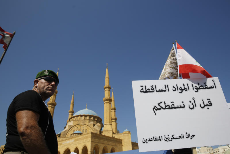 A retired  Lebanese soldier protests near the parliament building where lawmakers and ministers are discussing the draft 2019 state budget, in Beirut, Lebanon, Tuesday, July 16, 2019. The lawmakers have begun discussing the draft 2019 state budget amid tight security and limited protests against proposed austerity measures. The proposed budget aims to avert a financial crisis by raising taxes and cutting public spending in an effort to reduce a ballooning deficit. (AP Photo/Hussein Malla)