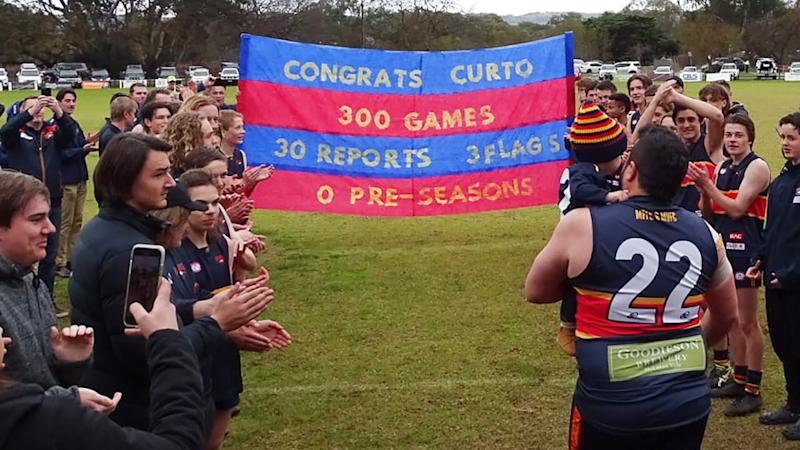The banner celebrating Mark Curtis' 300th match for the McLaren Football Club is pictured, which reads 'Congrats Curto, 300 games, 30 reports, 3 flags, 0 pre-seasons'.