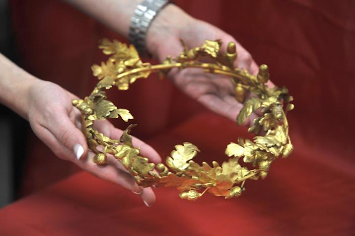 A police woman displays the wreath of gold oak leaves and acorns, date from roughly the 4th Century B.C. in Thessaloniki on Friday June 8, 2012. A 60-year-old retired policeman and a 41-year-old painter _ were arrested late the previous night east of the city after the artifacts were found during a routine traffic check. (AP Photo/Nikolas Giakoumidis)