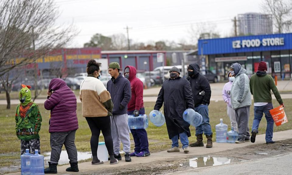 People wait in near freezing temperatures to fill containers with water in Houston.