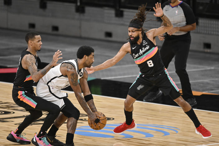 Brooklyn Nets' Kyrie Irving, center, grabs the ball as he is defended by San Antonio Spurs' Patty Mills (8) and Dejounte Murray during the first half of an NBA basketball game, Monday, March 1, 2021, in San Antonio. (AP Photo/Darren Abate)