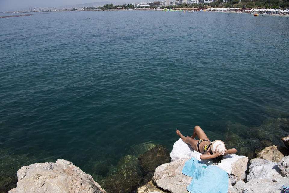 A woman sunbathes during a heatwave at a beach, in Alimos suburb, southern Athens, Greece, Monday, Aug. 2, 2021. The heat wave is expected to peak Monday, with temperatures inland ranging from 42 to 46 degrees Celsius (107.6 to 114.8 Fahrenheit). Temperatures will remain at 40 Celsius (104 Fahrenheit) or above in much of Greece until at least Friday, meteorologists say. (AP Photo/Michael Varaklas)