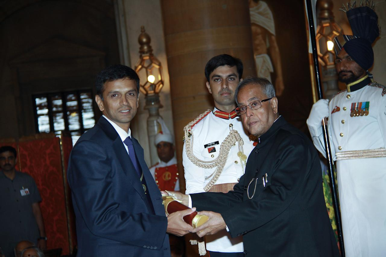 Indian President Pranab Mukherjee (R) presents the Padma Bhushan award to former Indian cricket captain Rahul Dravid during the presentation of the 'Padma Awards 2013' at The Presidential Palace in New Delhi on April 5, 2013.  Indian President Mukherjee presented two Padma Vibhushan, 10 Padma Bhushan and 42 Padma Shree awards to personalities from different professional backgrounds for their contribution to the nation.   AFP PHOTO/RAVEENDRAN        (Photo credit should read RAVEENDRAN/AFP/Getty Images)