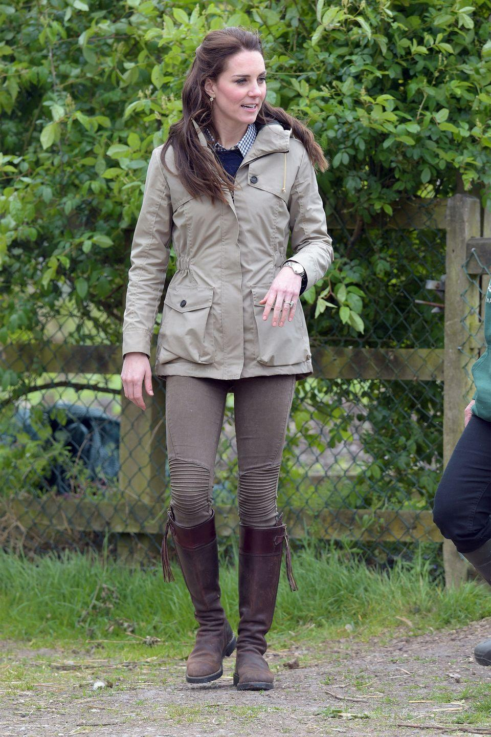 <p>In a navy sweater over a checkered shirt under a beige raincoat with Zara jeans and brown leather boots during a visit to the Farms for City Children charity in Gloucester</p>
