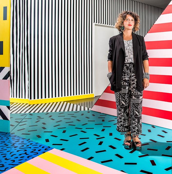 Designer and artist Camille Walala stands in the middle of one of her vibrant designs.