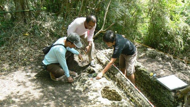 In this Feb. 26, 2011 photo released by the Philippine National Museum, Filipino archeologists gather items around a limestone coffin at Mount Kamhantik, near Mulanay town in Quezon province, eastern Philippines. Archeologists have unearthed remnants of what they believe is a 1,000-year-old village on the jungle-covered mountaintop in the Philippines with limestone coffins of a type never before found in this Southeast Asian nation, officials said, Thursday, Sept. 20, 2012. (AP Photo/Philippine National Museum, Joe Santiago) EDITORIAL USE ONLY, NO SALES