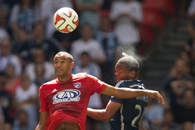 Sweat flies off the head of Vancouver Whitecaps' Carlyle Mitchell, right, of Trinidad and Tobago, after connecting with the ball against FC Dallas' Tesho Akindele during the first half of an MLS soccer game in Vancouver, British Columbia, on Sunday July 27, 2014. (AP Photo/The Canadian Press, Darryl Dyck)