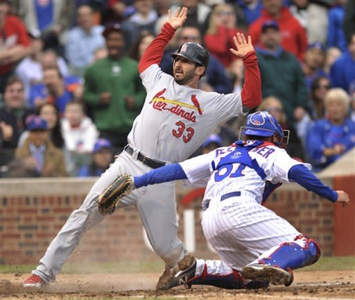 St. Louis Cardinals' Daniel Descalso (33) crosses home plate safely on a Matt Carpenter single as Chicago Cubs catcher Steve Clevenger tries to apply the tag in the third inning during a baseball game in Chicago, Wednesday, April 25, 2012. (AP Photo/Paul Beaty)