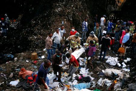 Rescue workers carry the body of a victim recovered out from a pile of garbage following a landslide when a mound of trash collapsed on an informal settlement at the Koshe garbage dump in Ethiopia's capital Addis Ababa