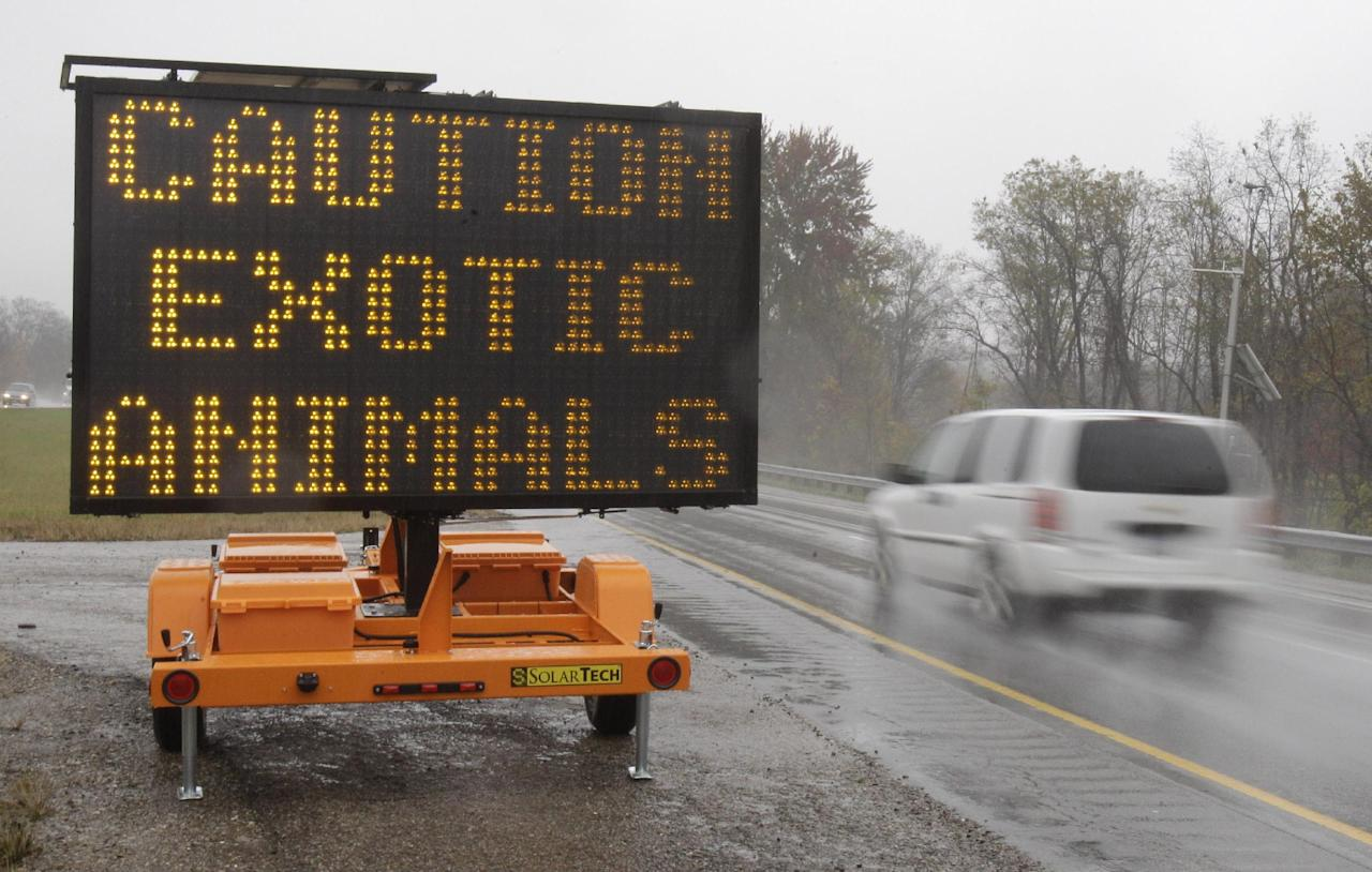 FILE - In this Oct. 19, 2011 file photo, a sign on I-70 near Zanesville, Ohio warns motorists that exotic animals are on the loose after their owner freed dozens of wild animals and then killed himself. An Ohio lawmaker plans Thursday, March 8, 2012 to introduce a proposal to ban new ownership of exotic animals in the state, months after authorities shot dozens of lions, tigers, bears and other wild creatures let loose by their suicidal owner. (AP Photo/Tony Dejak, File)