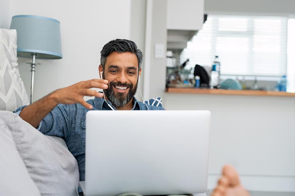 Happy mature man relaxing on couch while video calling using laptop at home. Latin man sitting on sofa and making a video call. Smiling middle eastern businessman doing online video chat while gesturing with hands.