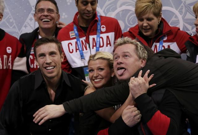 "Kirsten Moore-Towers and Dylan Moscovitch (L) of Canada react with their coach Kris Wirtz (R) and teammates in the ""kiss and cry"" area during the Team Pairs Free Skating Program at the Sochi 2014 Winter Olympics, February 8, 2014. REUTERS/Darron Cummings/Pool (RUSSIA - Tags: SPORT FIGURE SKATING SPORT OLYMPICS)"