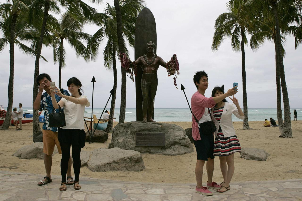 """Japanese tourists take """"selfies"""" in front of the Duke Kahanamoku statue in Waikiki as Tropical Storm Iselle passes through the Hawaiian islands, in Honolulu, Hawaii, August 8, 2014. The center of Tropical Storm Iselle made landfall on Hawaii's Big Island on Friday, bringing strong winds and heavy rain, knocking down trees and causing power outages ahead of a more powerful storm gathering strength behind it. REUTERS/Hugh Gentry (UNITED STATES - Tags: ENVIRONMENT SOCIETY)"""
