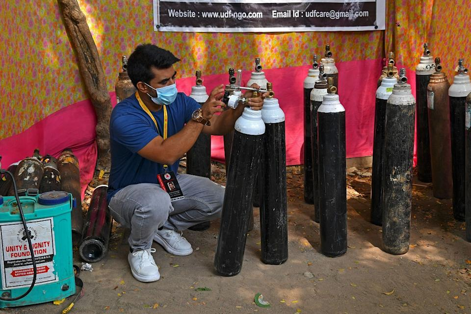 Mumbai resident Shahnawaz Shaikh, who sold his SUV car to raise funds in order to start free service to provide oxygen cylinders to the needy people amid Covid-19 checks the pressure of an oxygen cylinder at a distribution centre in a slum in Mumbai on April 28, 2021. (Photo by Indranil MUKHERJEE / AFP) (Photo by INDRANIL MUKHERJEE/AFP via Getty Images)
