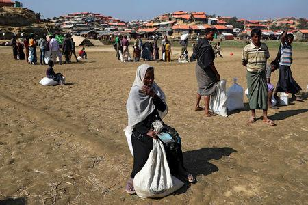 Rohingya refugees sit on the ground after collecting aid supplies in Thyingkhali refugee camp in Cox's Bazar, Bangladesh, January 21, 2018. REUTERS/Mohammad Ponir Hossain