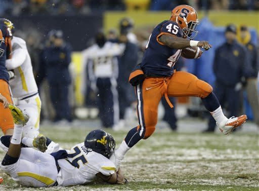 Syracuse running back Jerome Smith (45) escapes the grasp of West Virginia safety Darwin Cook (25) during the first half of the Pinstripe Bowl NCAA college football game at Yankee Stadium in New York, Saturday, Dec. 29, 2012. (AP Photo/Kathy Willens)