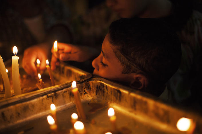 An Egyptian Coptic Christian child lights a candle in honor of the Virgin Mary at Al-Mahraq monastery in Assiut, Upper Egypt, Tuesday, Aug. 6, 2013. Islamists may be on the defensive in Cairo, but in Egypt's deep south they still have much sway and audacity: over the past week, they have stepped up a hate campaign against the area's Christians. Blaming the broader Coptic community for the July 3 coup that removed Islamist President Mohammed Morsi, Islamists have marked Christian homes, stores and churches with crosses and threatening graffiti. (AP Photo/Manu Brabo)