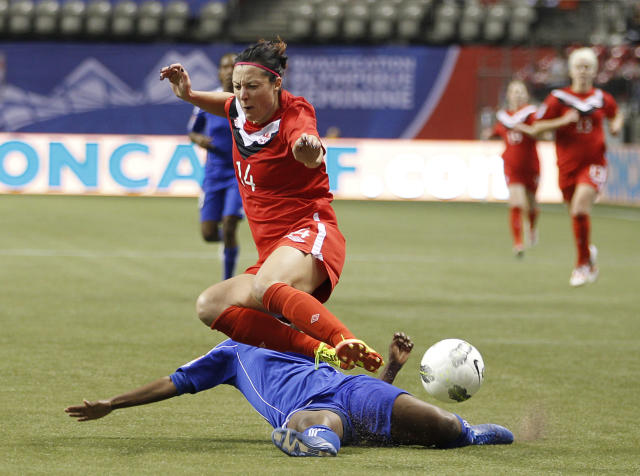VANCOUVER, CANADA - JANUARY 19: Melissa Tancredi #14 of Canada evades a slide tackle by Carmela Aristilde #3 of Haiti during the 2012 CONCACAF Women's Olympic Qualifying Tournament at BC Place on January 19, 2012 in Vancouver, British Columbia, Canada. (Photo by Jeff Vinnick/Getty Images)