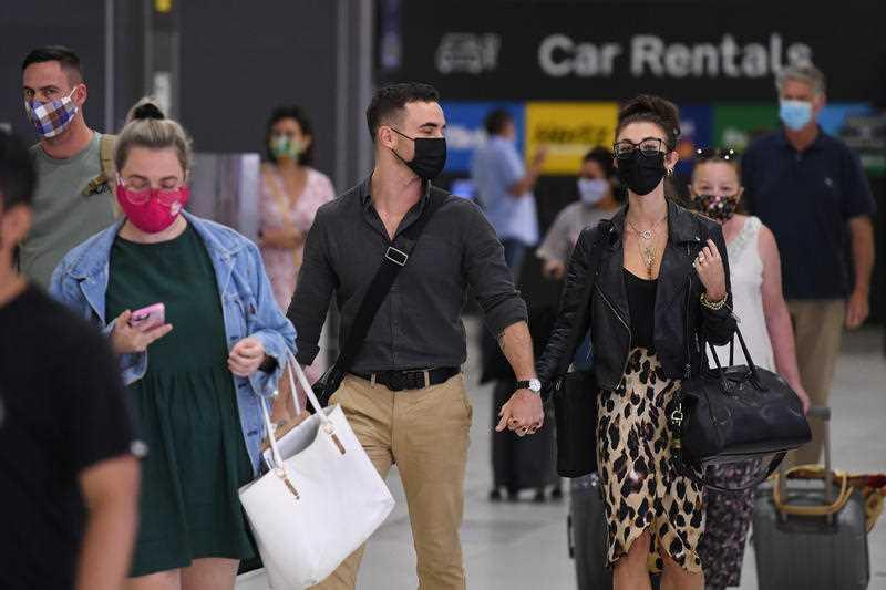 People wearing face masks are seen in the baggage collection area after arriving on Virgin Australia flight VA318 from Brisbane at Tullamarine Airport in Melbourne.
