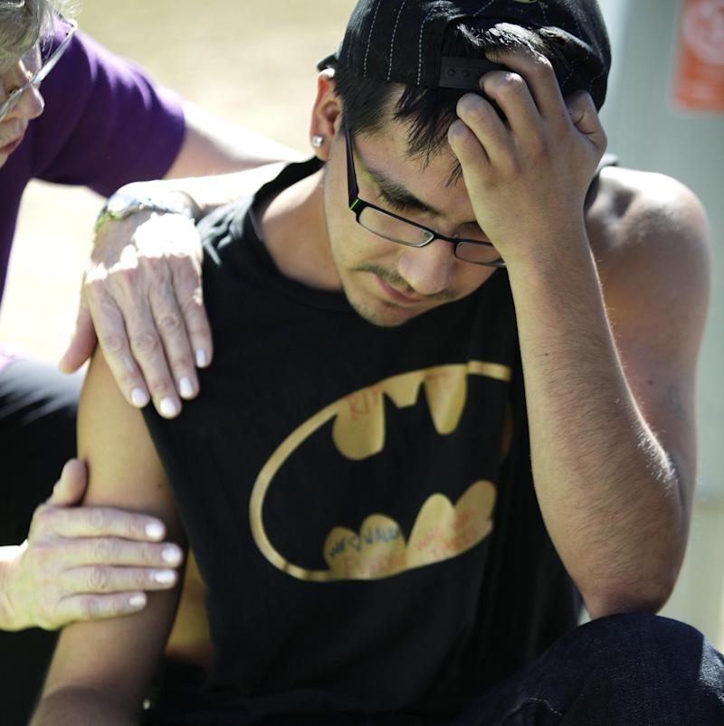 "Isaac Pacheo, who said he was a good friend of theater shooting victim Alex Sullivan, is comforted, Saturday, July 21, 2012, as he visits a memorial near the movie theater in Aurora, Colo.  Twelve people were killed and dozens were injured in the attack early Friday at the packed theater during a showing of the Batman movie, ""Dark Knight Rises.""   Police have identified the suspected shooter as James Holmes, 24. (AP Photo/Ted S. Warren)"