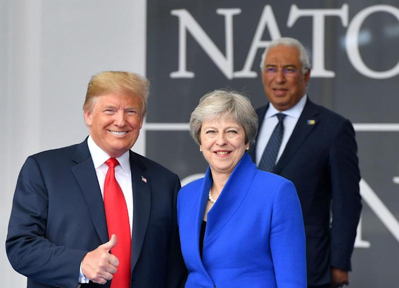 US President Donald Trump (L) gestures as he poses alongside Britain's Prime Minister Theresa May (R) as Portugal's Prime Minister Antonio Costa (TOP) looks on during the opening ceremony of the NATO (AFP/Getty Images)